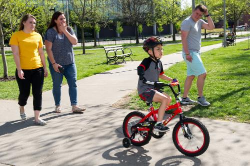young boy riding bicycle using adaptive device, with three UI engineering students following on foot
