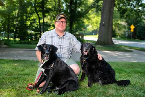 University of Iowa anthropologist Andrew Kitchen sitting with his two dogs