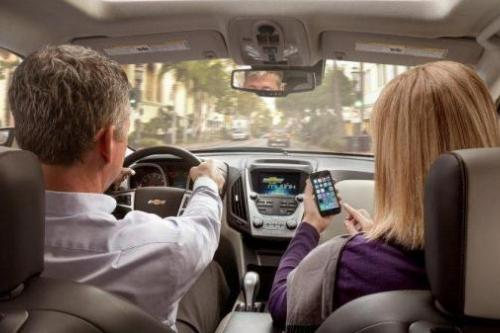 A man and a woman sit in the front seat of a car while the woman looks at a mobile device