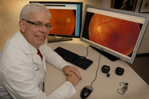 man sitting at desk with monitors showing eye images
