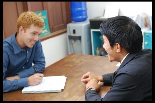 UI doctoral student in linguistics, Douglas Cole, interviews a resident of Laos for his research while abroad on the Lao language.