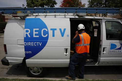 An employee opens the door of a DirecTV van.