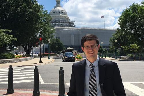 man standing with capitol in background