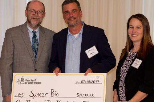 SynderBio's Michael Henry accepts check from Dan Reed and Jordan Kaufmann
